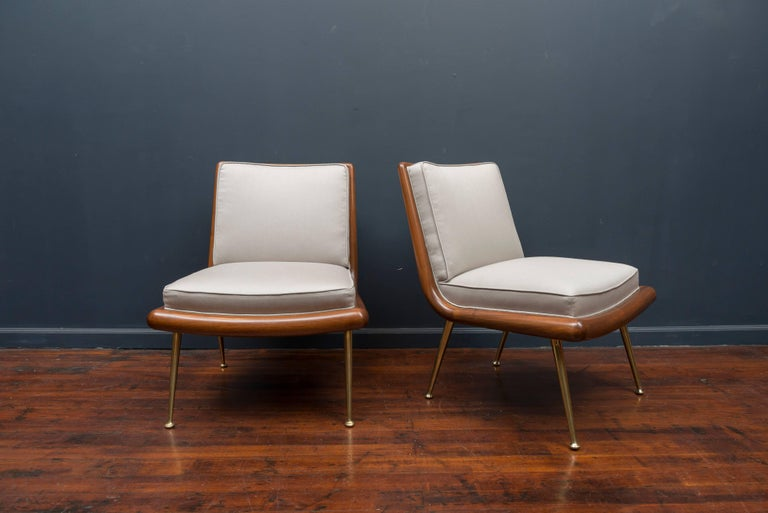 Rare pair of T.H. Robsjohn-Gibbings design lounge chairs for Widdicomb Furniture Co. Newly refinished walnut bull nose frames on polished brass telescoping legs. New light silver Maharam satin wool upholstery.