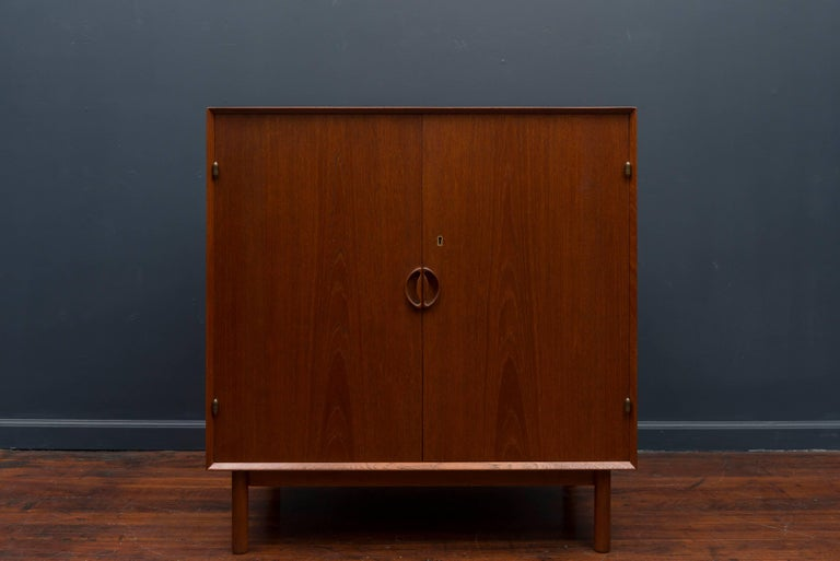 High quality design and construction two-door cabinet by Peter Hvidt & Orla Mølgaard. Oiled teak wood with brass hinges and fitted interior.