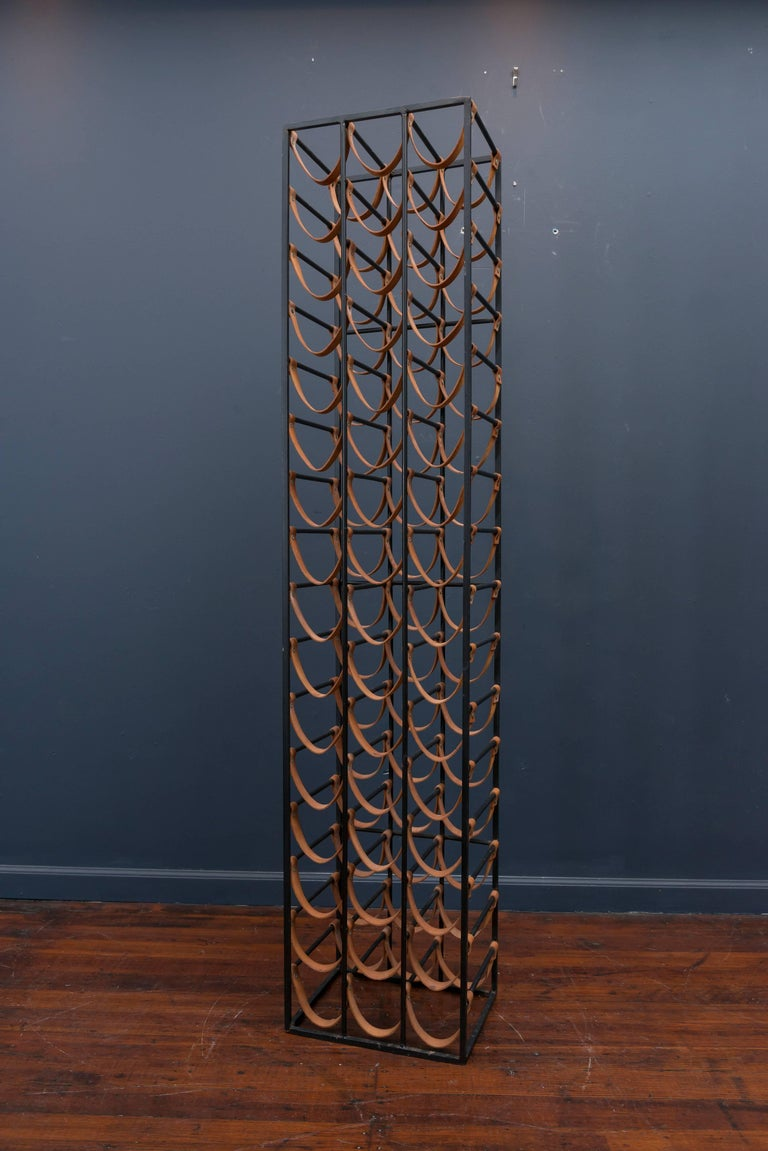 Arthur Umanoff flat black steel and natural leather strapped wine rack. Very good original condition, holds 48 bottles.