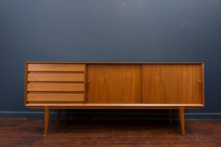 Superior design and construction is exemplified in this Danish Modern teak credenza designed by Gunni Omann, Denmark. Newly refinished with solid teak drawers and adjustable shelves on sculpted tapering legs.