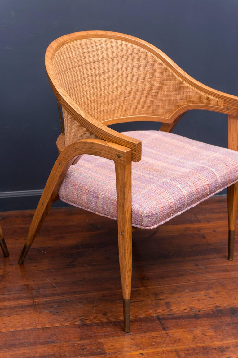 Elegant design armchair by Edward Wormley for Dunbar Furniture co. Berne Indiana Model 5480. Excellent original condition examples made from oak with caned backs and brass sabots. Sold in pairs only, two available.