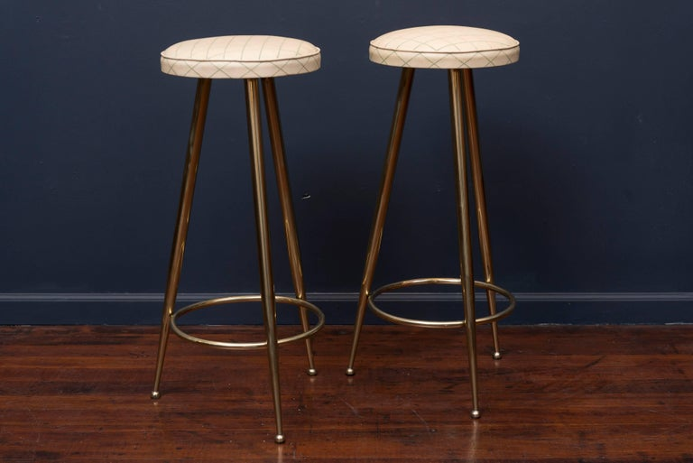 Pair of newly polished brass bar stools made in Italy with original vinyl upholstery.