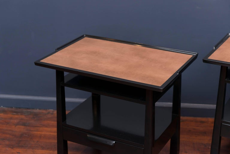 Pair of Edward Wormley design side tables made from solid mahogany with leather insert tops. Sculpted single drawer pull with a gallery trimmed top on tapering legs, newly refinished, labeled.