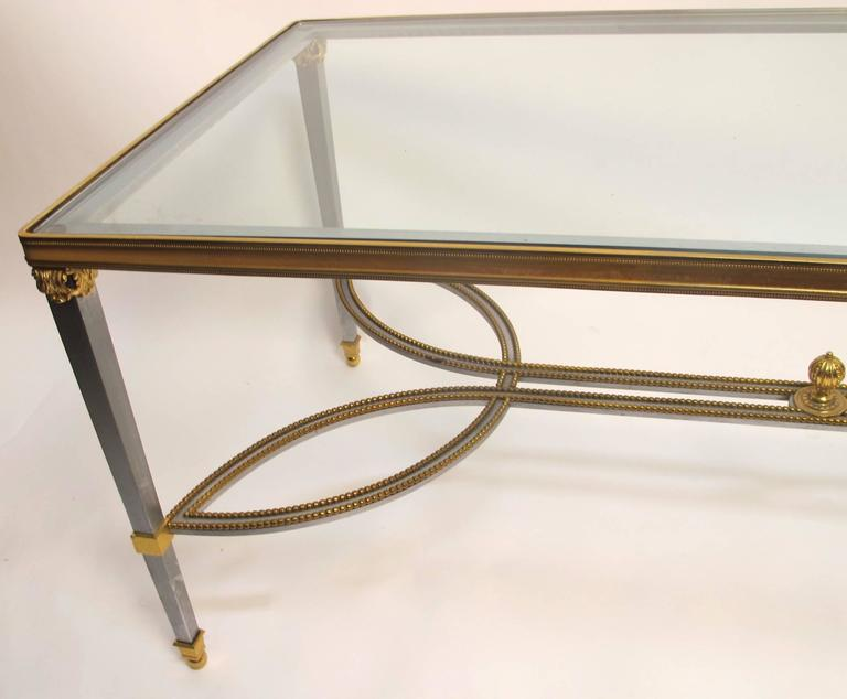Neoclassical Revival style steel and gilt brass trim coffee table with inset glass top. This extremely well made piece has a number of interesting design features including a beaded detail and finial on its stretchers and an acanthus leaf capitol