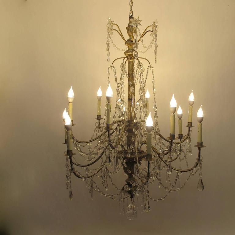 An exceptional 18th century or early 19th century Italian twelve-arm candle light chandelier. Silver giltwood and iron frame with crystal pendants and glass swags. Recently re-conditioned and electrified.