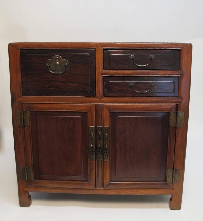 An usual elmwood and rosewood Chinese cabinet. Having an inset rosewood panel on the top, doors and drawers of rosewood, and the body of the chest is Chinese elmwood. Original brass pulls and hardware. Interesting molding detail around the entire