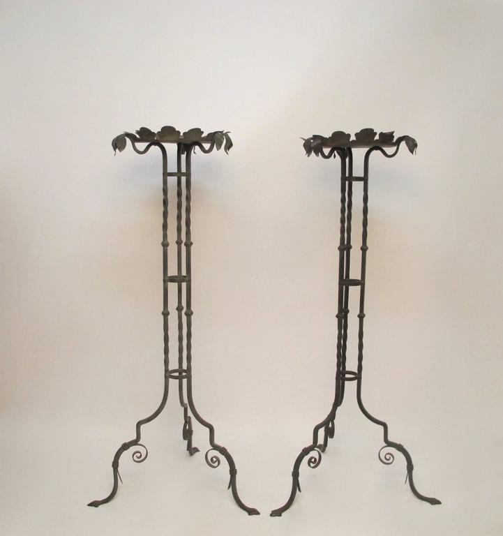 A pair of iron plant stands with verdigris finish. Triple leaf decoration at the end of each support and scallop saucer holder. Early 20th century.