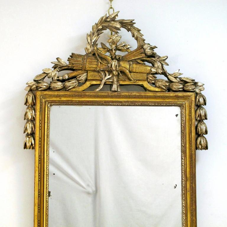 Highly unusual white gold gilt Louis XV carved mirror with swags, of leaves, crossed arrows and quiver below a crown wreath of laurel leaves, French, circa 1780.