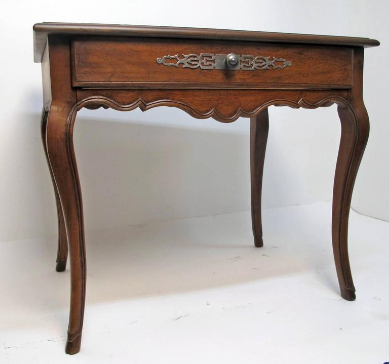 Louis XVI Walnut Writing Table with inset brown leather top with tooling, standing on cabriole legs ending on cloven hoof feet and having single drawer with steel decorative plate and knob.  French Circa 1780.