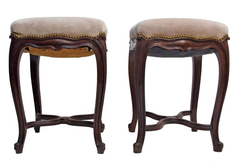 A pair of beautifully carved rosewood stools or tabourets with nailhead detail. In need of new upholstery (shows age and wear), France, 19th century.