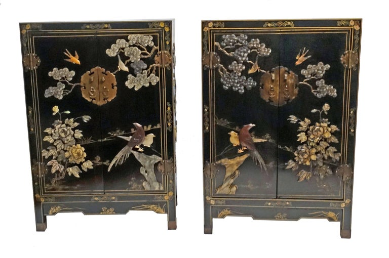 A pair of black lacquer cabinets with elaborate hard stone inlay of birds, trees and flowers and having fine brass hardware. Originally purchased in Hong Kong in the 1950s-1960s.