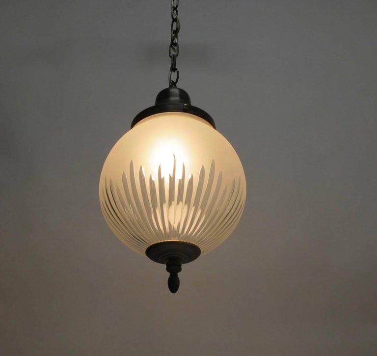 Hanging frosted and cut glass pendant orb light fixture with a single bulb having patinated bronze finish on the fittings and with a bronze finished canopy. Newly re-wired, chain can be adjusted to desired length. American, early 20th century.