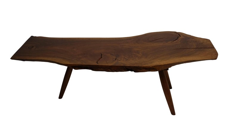 Beautifully figured walnut plank coffee table with three knots standing on tapering legs. American, circa 1970.