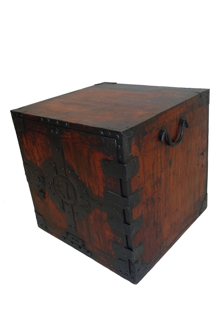 Small shipboard chest with iron decoration and fitted interior. Elaborate iron detail on the door, opening to a single long drawer over two short drawers above a single long drawer, with iron handles, Japan, 19th century.