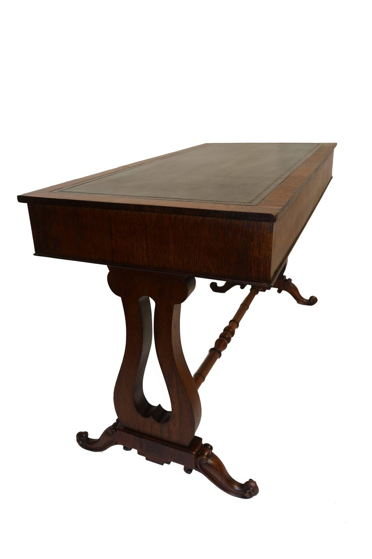 A handsome Regency style rosewood sofa table or gentleman's desk with inset black leather writing surface with gold tooling. Having two drawers, one of the drawers has divisions, lyre shape supports and sitting on scrolled feet. England, circa 1840.