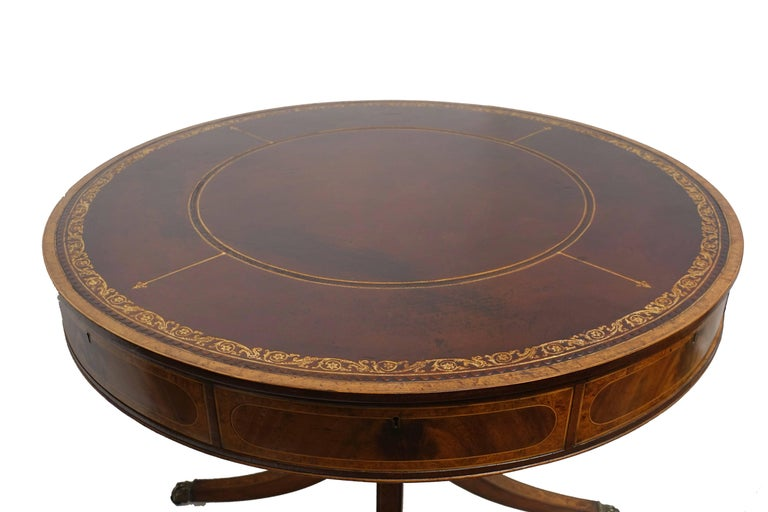 Handmade mahogany rent table or library/centre table with original inset leather surface having hand tooled gilt edge detail. Table has four working drawers and four blind drawers, standing on an elegant four legged pedestal base. Recently