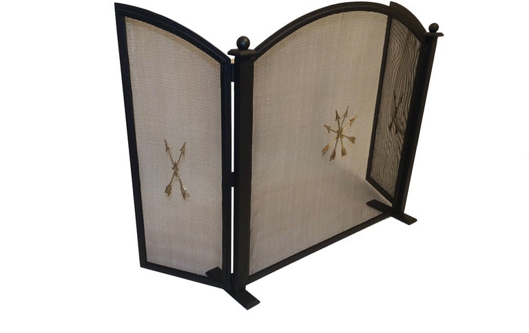 French Empire style black painted wrought iron three panel fireplace screen having brass crossed arrows appliqué decoration, American, circa 1940s. Fully reconditioned.