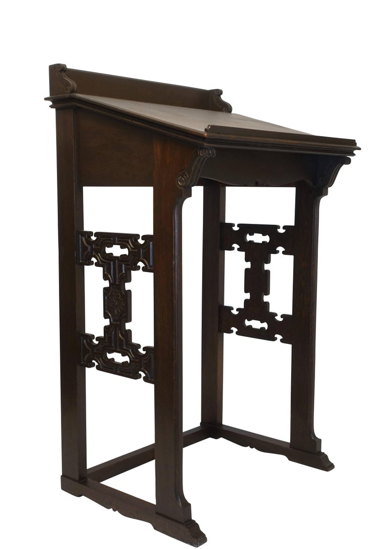 A standing oak podium with molding edges and carved detailing. American, late 19th century.