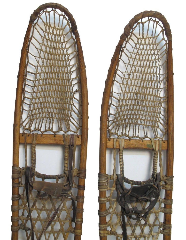 A large pair of antique snowshoes having a wood frame, rawhide webbing and leather straps. Marked E. H. Co. Wallingford Vermont US.