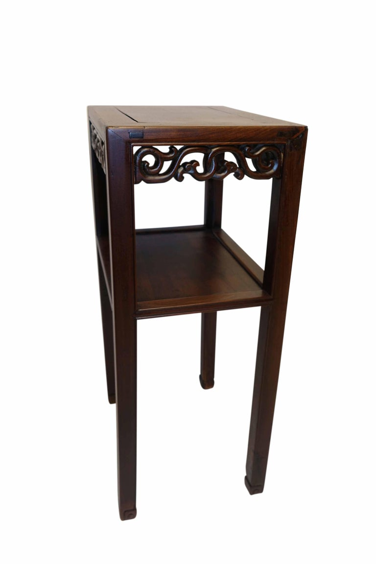 Wonderful Chinese stand or pedestal with richly carved apron around all four sides above a recessed panel lower shelf, standing on slender legs ending in cuffed feet, China, mid-19th century.