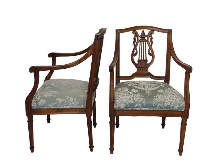 A pair of neoclassical carved walnut fauteuils with carved lyre shape backsplat, sitting on carved and fluted legs. Recently re-upholstered, Northern Italy, 18th century.