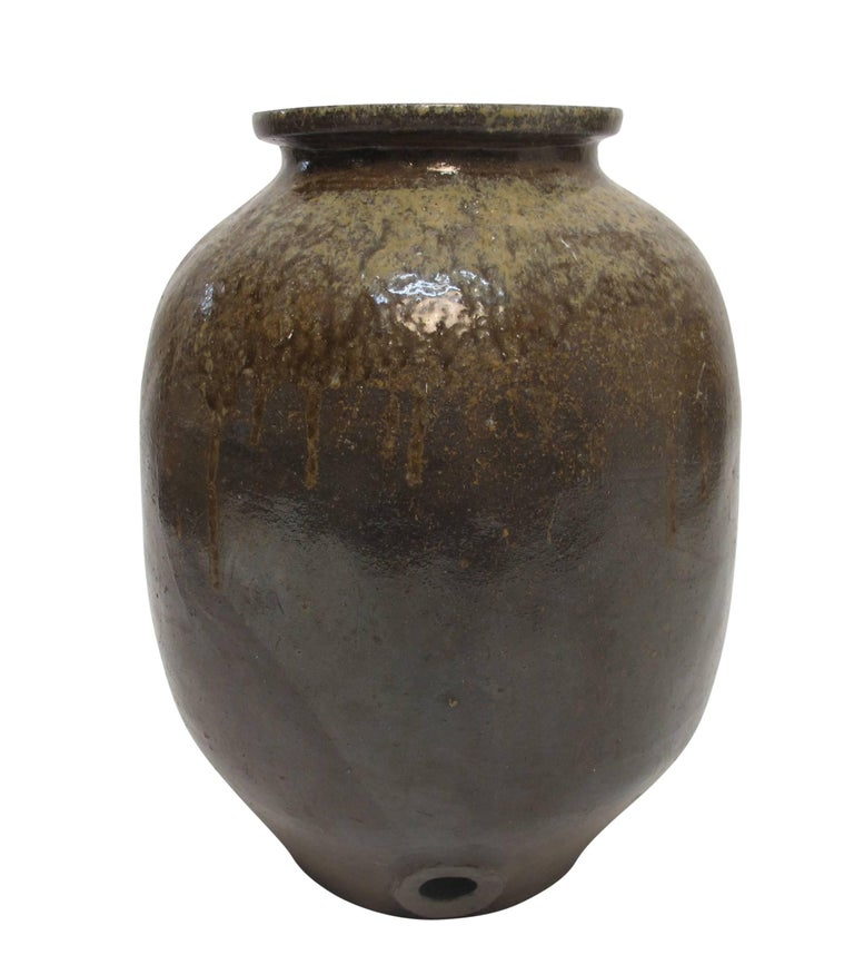 A large heavily glazed stoneware sake jar or pot. Wonderful colors and shape. Presumedly the hole on the side would have had some kind of spout originally, Japan, 19th century.