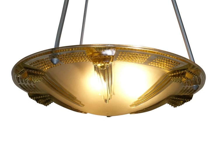 A unique greenish golden color tinted glass hanging pendant light fixture. The design is of graduated and raised towers pointing towards the center, and having a rim of graduated raised nubs, suspended from three silvered hexagonal shaped arms.