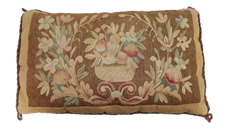 Antique tapestry fragment with basket of fruit and floral design made into a pillow with down cushion. Continental, early 19th century. Shows expected light wear and age.