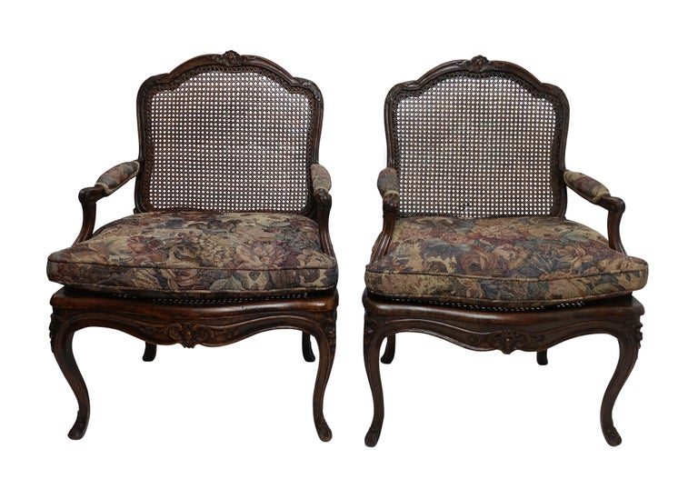 Pair of finely carved Regence Fauteuils with hand caned backrests and seats and vintage tapestry style upholstered fitted cushion. The frame of the chairs carved with acanthus leaves and the shaped crest rail centred with a shell carving as is the