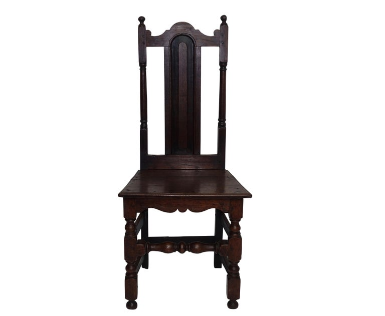 Oak side chair with panel back splat and arched top rail, having a plank seat above two turned front legs and shaped apron. Peg and tenon construction, England, circa 1730.