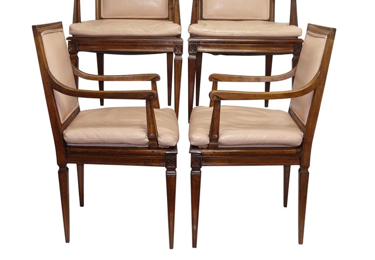 A set of four neoclassical style beechwood armchairs with sculpted frame and standing on tapering square legs, with leather upholstery. Italy, late 19th-early 20th century.