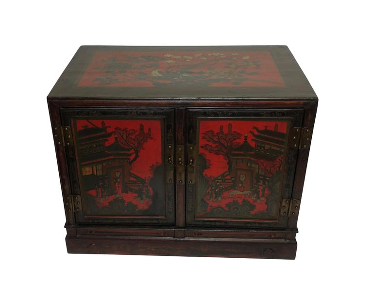A pair of red and black lacquer ceremonial robe cabinets with a painted garden scene of figures and flowers, having brass hardware and handles. The back side has been lacquered and painted as well. China, Qing dynasty, mid-19th century.