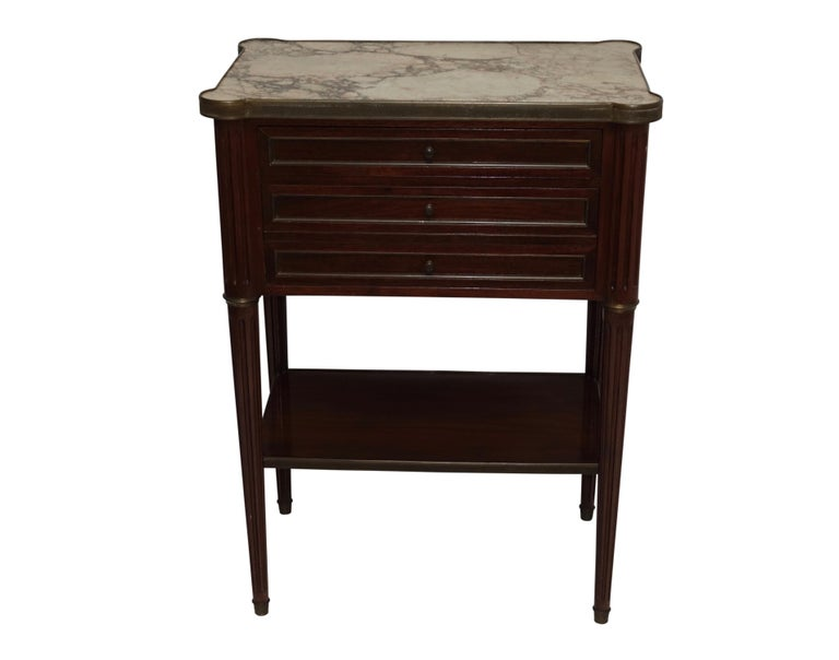 Louis XVI style mahogany bedside table with a marble top, trimmed with brass banding above two drawers and having brass moulding around the recessed panels, flanked by fluted columns and brass collars at the top of the tapering legs ending in brass
