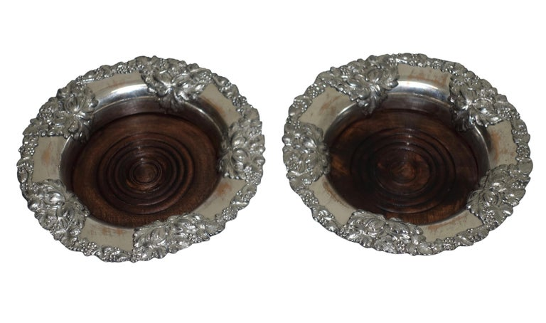 A pair of antique Sheffield silver plate wine coasters with grape leaves, a grape design border and inset wood bottom. England, 19th century, circa 1860.