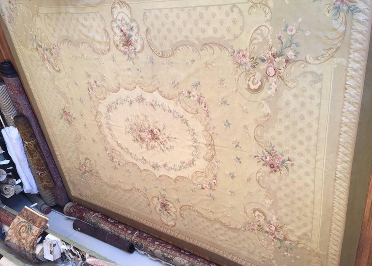Wonderful French Aubusson flat handwoven tapestry rug of elegant design with subdued colors and delicate floral motifs. Rich and soft ivory ground decorated around a centered floral medallion banded with floral sprays and acanthus leaves.