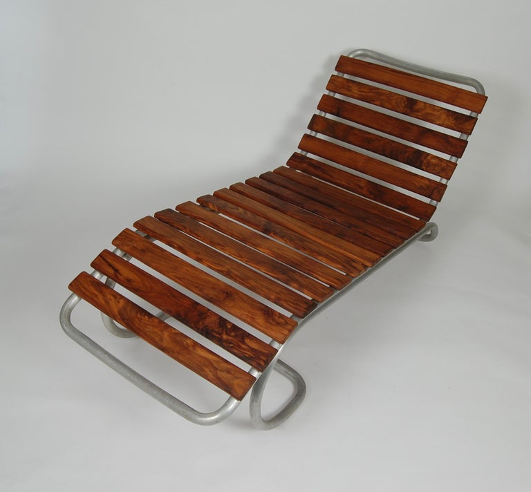 Intended as an outdoor chaise this piece has the duality for either indoor or outdoor usage. The bent aluminum frame has dramatic lines and the Claro walnut adds richness and form to the piece.