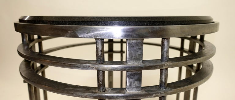 Black beveled granite stone top on a round brushed steel four ring base side or occasional table. 