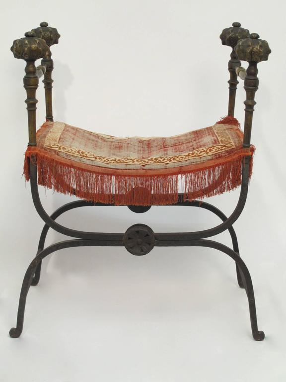 A 19th century savonarola style chair or bench, all hand wrought iron with four ornate bronze finials. Original unrestored condition.
