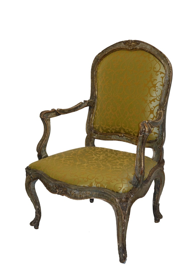 Beautifully carved wood and hand-painted armchair, retaining most of its original painted finish. This chair is a good size with a generous seat. Recently reupholstered in a silk fabric. Italy, 18th century.