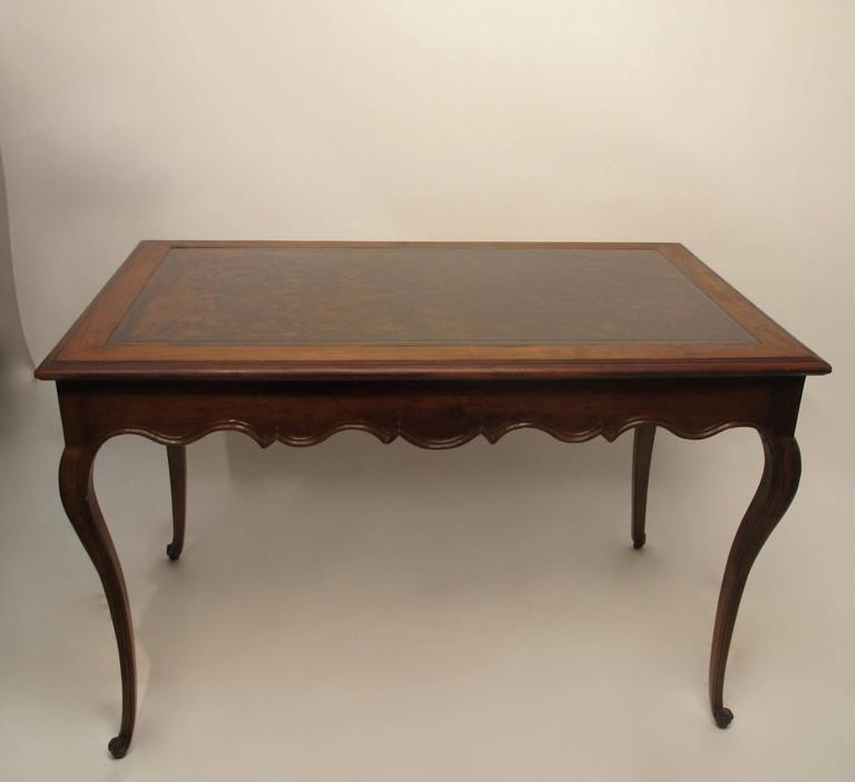 A graceful Louis XVI style carved walnut writing table with inset leather top, having a single drawer at one end. In beautiful condition. France, circa 1760.