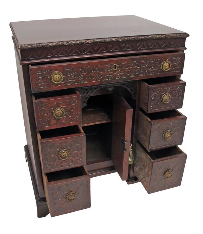 Georgian Mahogany child's desk with blind fret carving to the apron around the top and the drawer fronts.  Single long drawer above  above pair of three drawers with brass ring pulls flanking knee hole cupboard standing on bracket feet.  English,