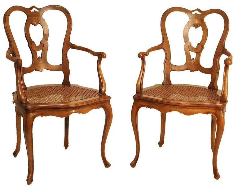 A pair of fine quality and beautifully carved walnut armchairs with caned seats. These chairs have a nice generous size seat, and are sturdy and sound. Cushions are in good condition, ready for upholstery, Italy, mid-20th century.