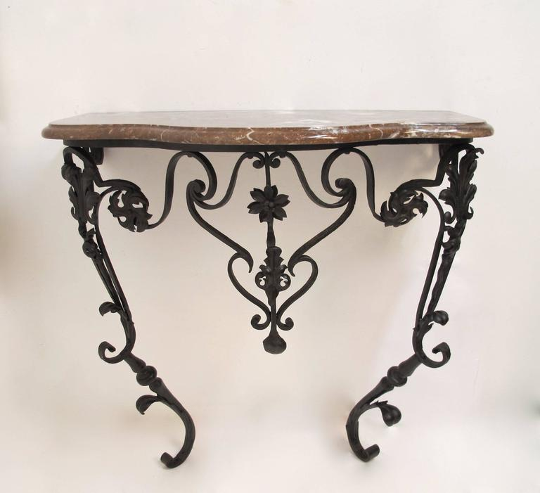 A Wall Mounted Wrought Iron Base Console Table With Fl And Scrolled Designed Having