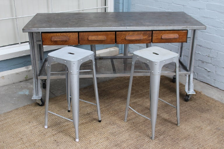 1960s Industrial table and four chairs, table can be used as a kitchen island or work table because of the wheels it can be easily move around the loft or kitchen. Also four antique oak wooden drawer as artist touch.