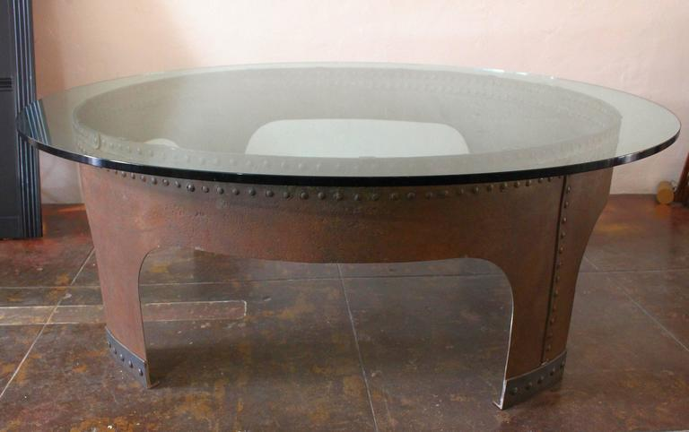 1970s creation of Gimo Fero a Venation artist. Round 3/4 of inch glass on 1918 military iron cistern base done by artisan black smith. Table is surround with ten Industrial stools in original condition. Table can be presented as a dining table.