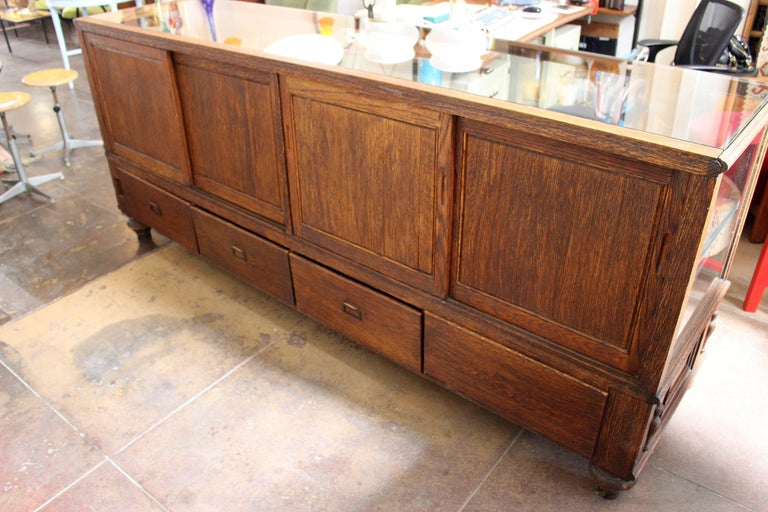 Arts & Crafts glass case, oak base in original condition new glass top, four drawers on the bottom, mirrors on the back sliding doors. Sign Grand Rapid Equipment.