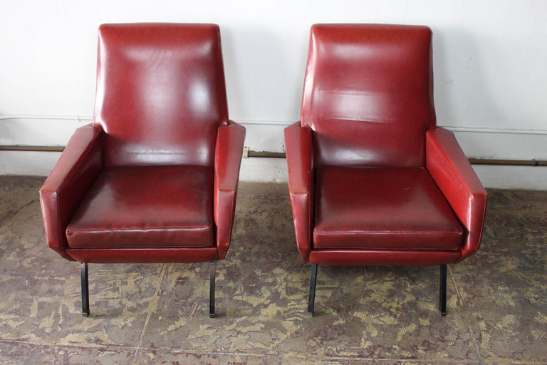 1950s Pair of club chairs original red skay upholstery metal legs and brass boots.