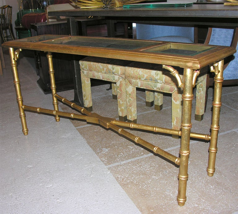 Faux bamboo gilt console or sofa table, with glass inset tops. Distressed finish with gold worn in spots revealing the red under color with a good bit of patina on entire piece.
