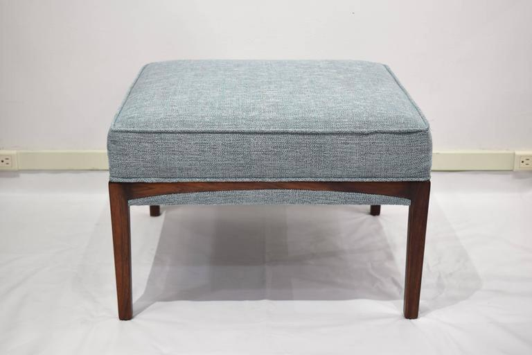 Pair of 1960's mid century modern benches or ottomens featuring a curved inlaid base in a natural walnut finish with a pale seafoam blue upholstered top.