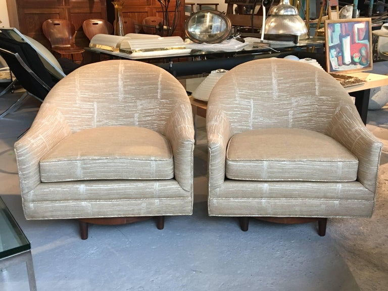 Pair of 1960s swivel lounge chairs by Selig, with walnut bases; all new upholstery, excellent sturdy construction.